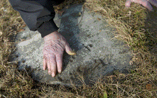 Dick Roberts wipes an old tombstone